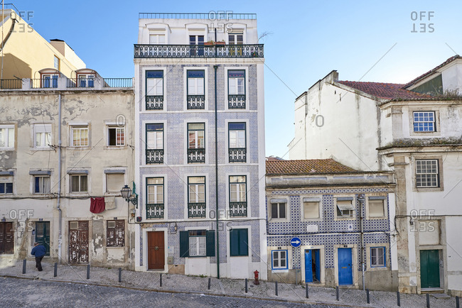 Lisbon, Portugal - 21 December, 2017: Man walking up hill past  apartment buildings decorated with Moorish tiles