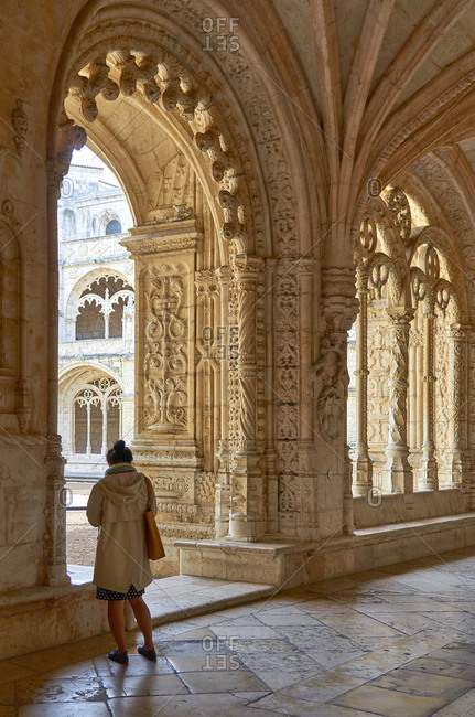 Woman standing in cloister of the Jeronimos Monastery, Lisbon, Portugal