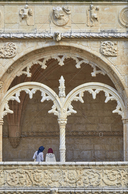 Two women standing under arch of the Jeronimos Monastery, Lisbon, Portugal