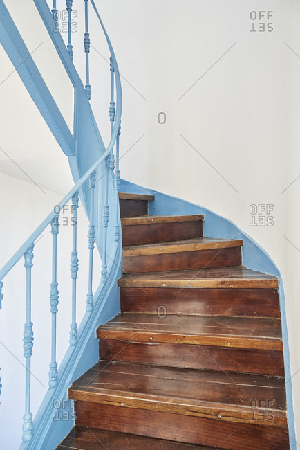 Old winding wooden staircase with a blue railing