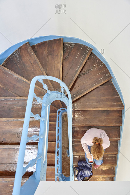 Overhead view of woman sitting on winding wooden staircase with a blue railing