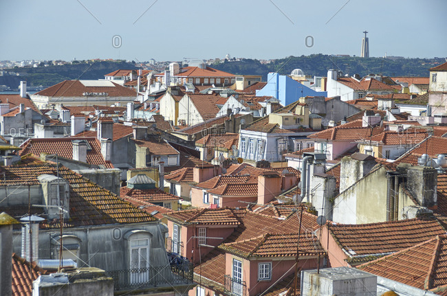 Elevated view of buildings in Lisbon, Portugal with Cristo Rei Christ Statue in distance