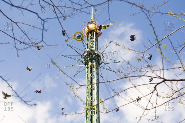 May 2, 2011: A tall carousel ride at Tivoli Gardens as viewed through the branches of a tree. Copenhagen, Denmark