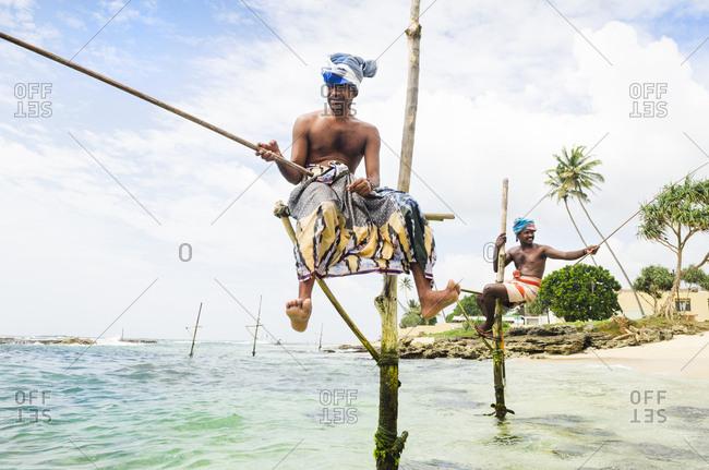 Two Sri Lankan fishermen sitting on wooden stilts and fishing at Weligama Bay, Sri Lanka