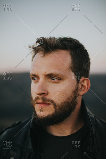Portrait of a man wearing a leather jacket looking off to the side