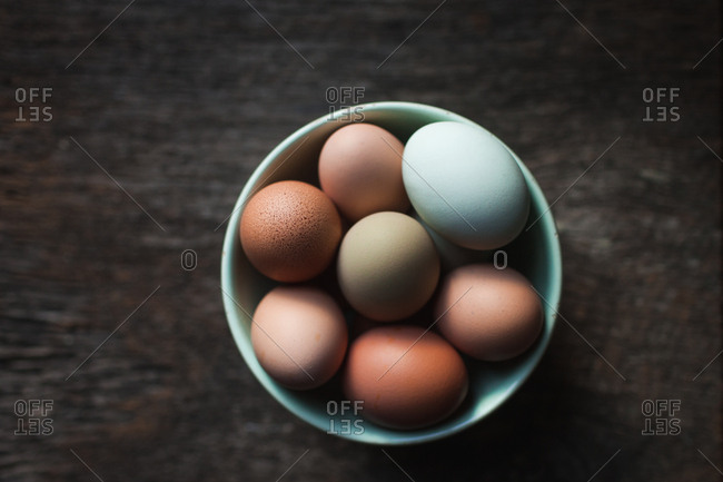 Overhead view of a bowl full of multicolored eggs