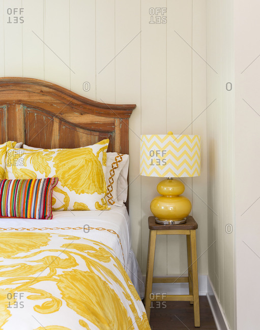 Bed in home interior with yellow decor