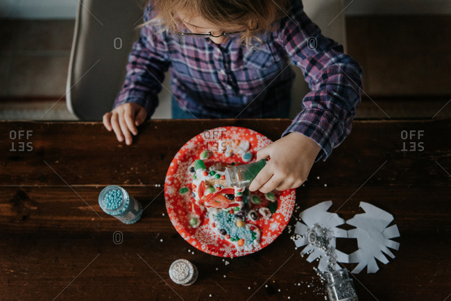 Overhead view of little girl building a gingerbread house