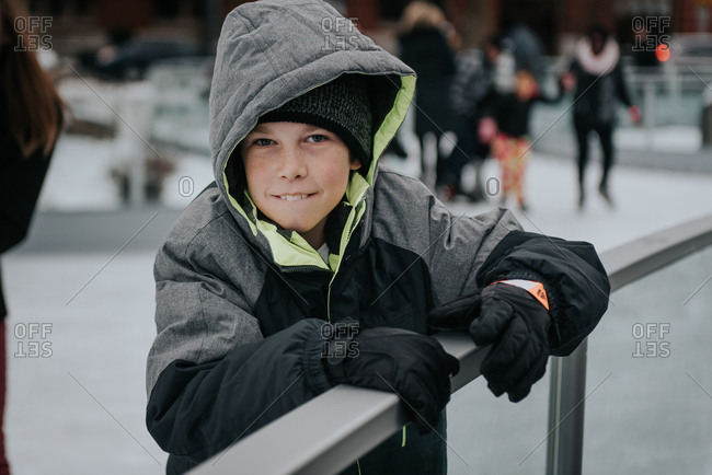 Boy holding railing while ice skating