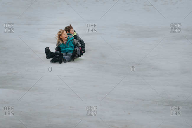 Two kids sledding down a hill