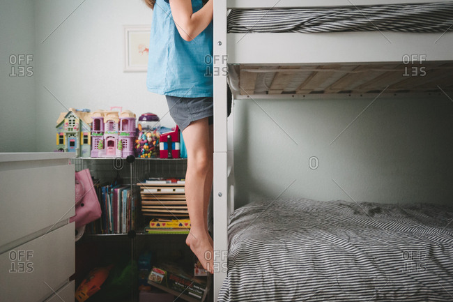 Girl climbing on end of bunk bed