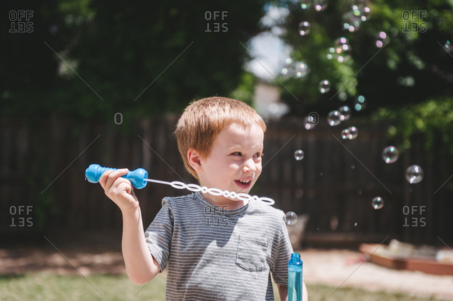 Little boy blowing bubbles in backyard