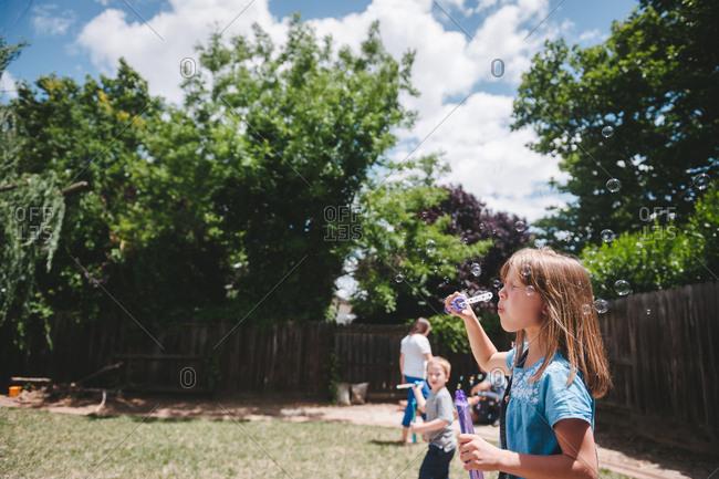 Children blowing bubbles in backyard