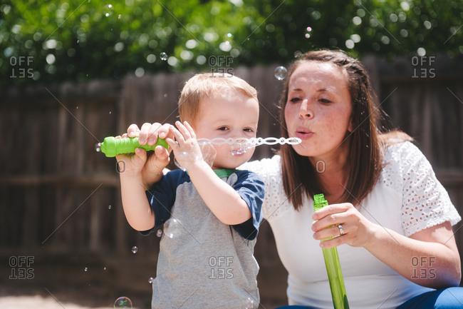 Mom helping little boy blow bubbles in backyard
