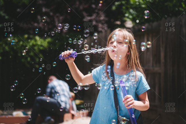Girl blowing bubbles in backyard