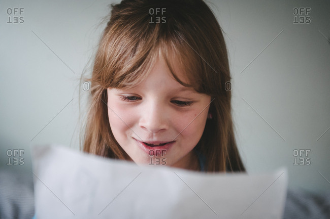 Smiling girl reading from sheet of paper