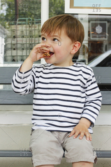 Happy young boy eating a cookie