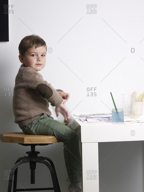 Toddler boy eating cookies and painting in studio