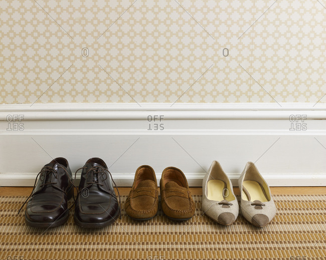 Three pairs of shoes representing different family members in a the hallway of a stylish home