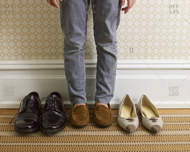 Child standing in between parent's shoes in hallway of a stylish home