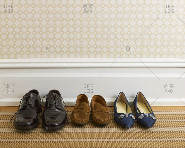 Father's dress shoes, mother's heels and child's loafers in hallway of stylish home