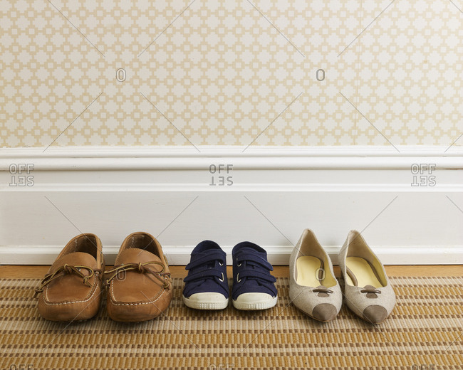 Mother's, child's and father's shoes in a row in hallway of a stylish home