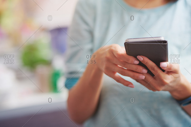 Woman using smartphone at the kitchen