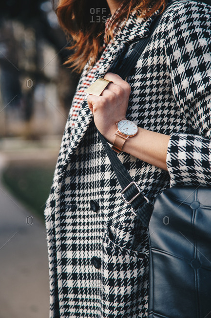 Woman wearing houndstooth jacket and stylish watch