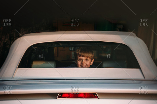 Smiling boy looking out the back window of a car