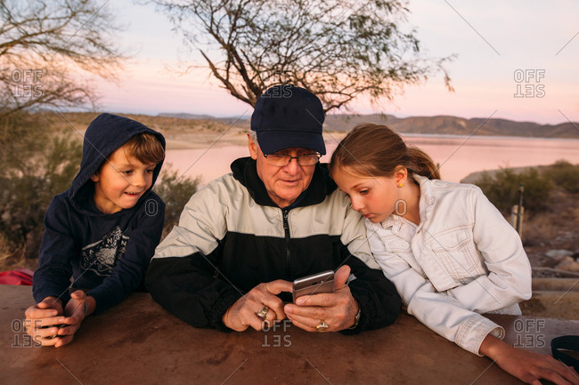 Grandfather using smartphone with grandchildren