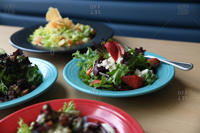 Variety of healthy salads served on colorful plates