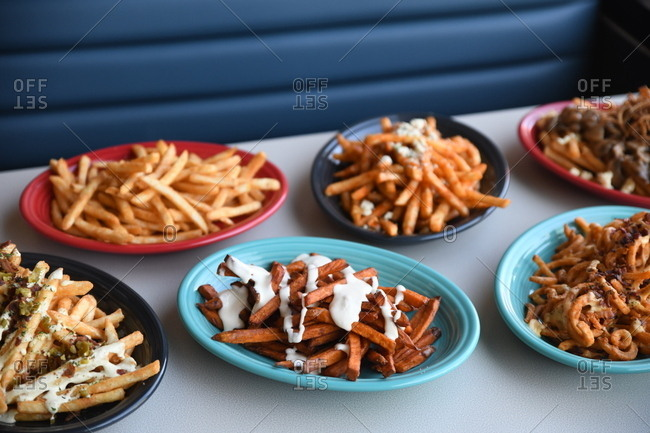 Variety of French fries topped with sauce served on colorful plates