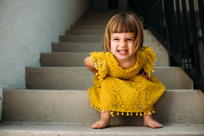 Little girl sitting on steps making a funny face