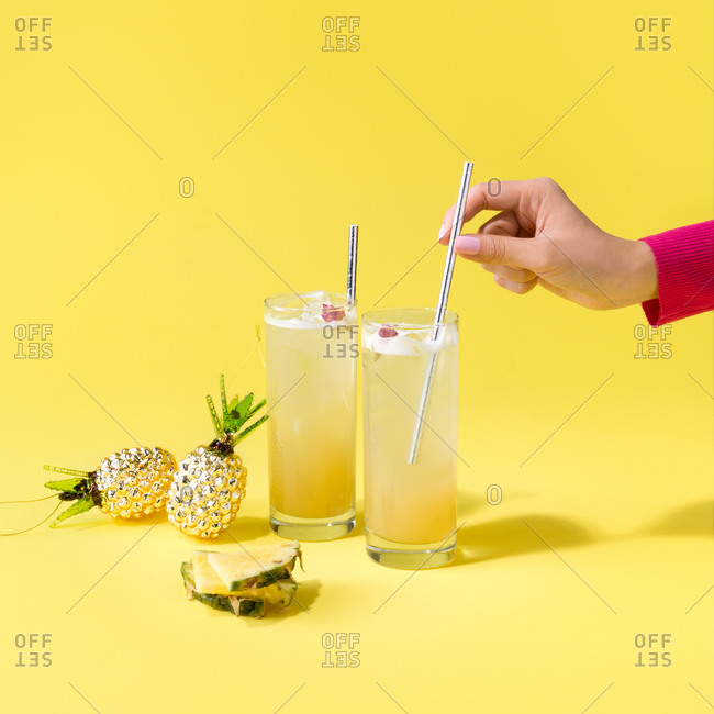 Female hand stirs pineapple cocktail