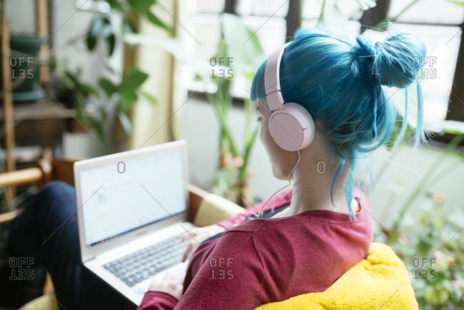 Young woman with blue colored hair and headphones listen to music from her laptop