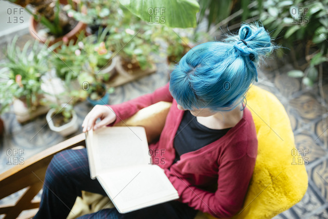 Young woman with blue colored hair reading a book