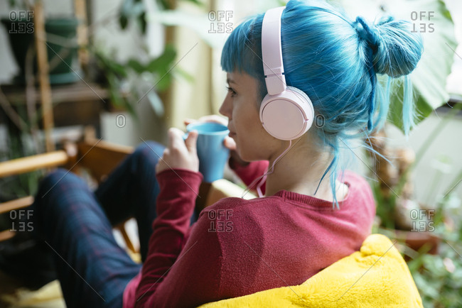 Young hipster woman with stylish blue dyed hair relaxing and drinking coffee at home