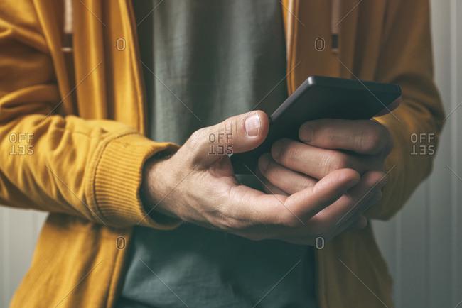 Man unlocking smartphone with fingerprint scan sensor.