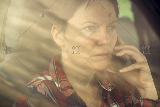 Worried woman talking on mobile phone in car.
