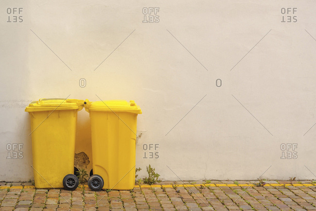 Two yellow recycling bins on street.