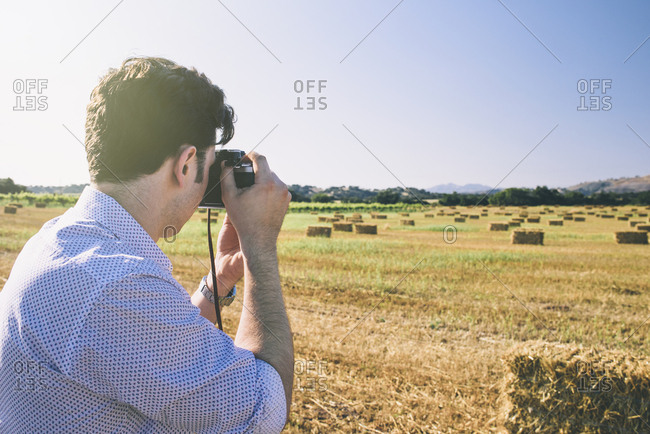 Young man photographing with camera while standing on agricultural field during sunny day