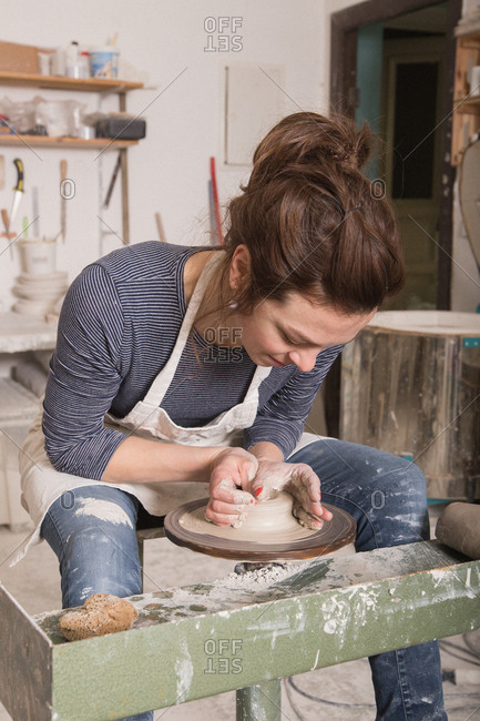 Caucasian woman is shaping pottery clay on a pottery wheel in a ceramic workshop.