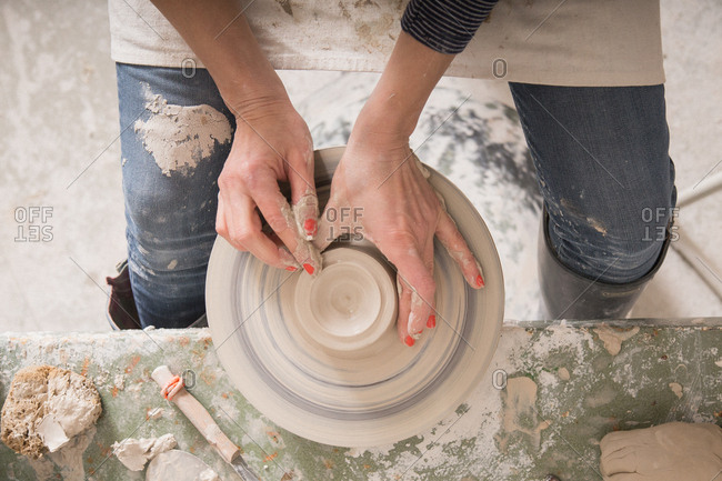 A ceremic artist shaping pottery clay on a pottery wheel in a ceramic workshop.