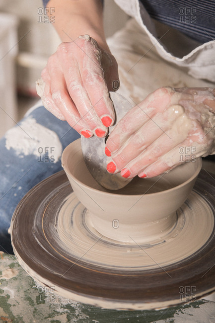 Close up of a woman's hand shaping pottery clay on a pottery wheel in a ceramic workshop.