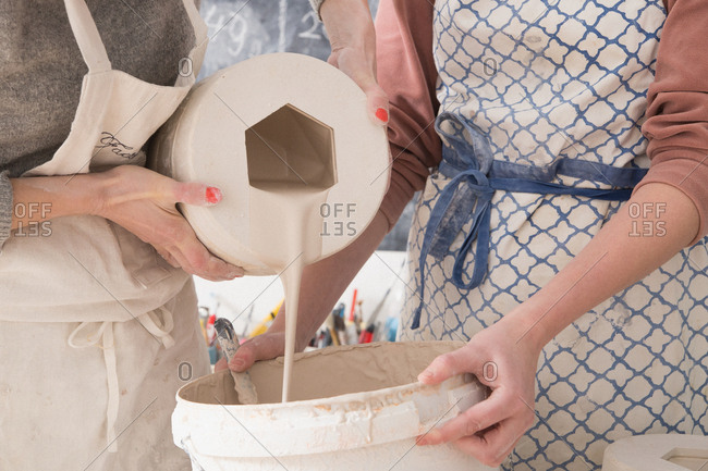 Two ceremic artists are slip casting ceramics in a pottery workshop.