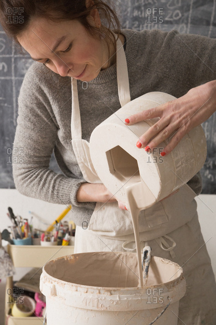 A ceremic artist is slip casting ceramics in a pottery workshop.