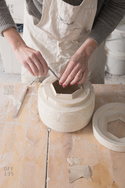 A ceremic artist is in the process of slip casting ceramics in a pottery workshop.