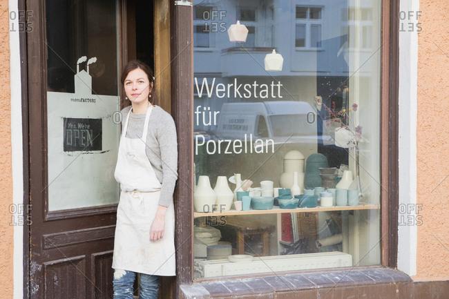 A ceramic maker portrayed outside her pottery workshop.