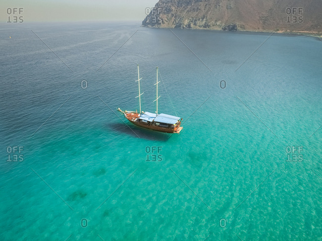 Aerial view of a sailboat in the picturesque bay of Khorf Fakkan, United Arab Emirates.