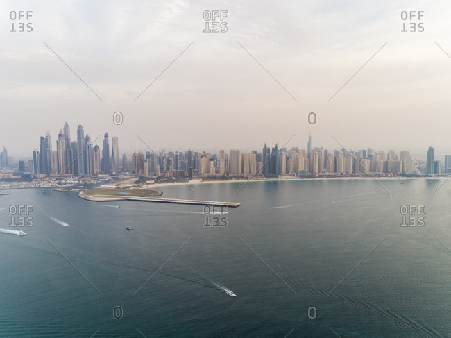 Aerial panoramic view of skyscrapers and boats navigating in the bay of Dubai, United Arab Emirates.
